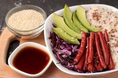 alimento hawaiano della ciotola del colpo un piatto di riso, del salmone, dell'avocado, del cavolo e del formaggio vicino alla sa immagine stock libera da diritti