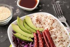 alimento hawaiano della ciotola del colpo un piatto di riso, del salmone, dell'avocado, del cavolo e del formaggio vicino alla sa fotografia stock