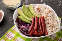 alimento hawaiano della ciotola del colpo un piatto di riso, del salmone, dell'avocado, del cavolo e del formaggio vicino alla sa fotografie stock