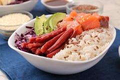 alimento hawaiano della ciotola del colpo un piatto di riso, del salmone, dell'avocado, del cavolo e del formaggio vicino alla sa fotografia stock libera da diritti