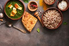 Alimento indiano Paneer di Palak o curry della ricotta e degli spinaci, riso, spezie, naan, su un fondo scuro Vista superiore, sp fotografia stock