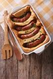 Alimento inglês: sapo no furo em um prato do cozimento Parte superior vertical foto de stock