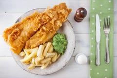 Alimento inglês tradicional - peixe com batatas fritas com sopa de ervilhas Foto de Stock Royalty Free
