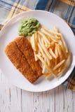 Alimento inglese: pesce fritto in pastella con il primo piano delle patate fritte verticale Fotografie Stock Libere da Diritti