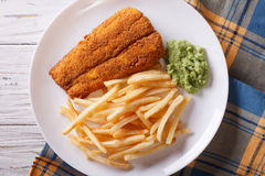 Alimento inglês: peixes fritados na massa com close-up das microplaquetas horizont Foto de Stock Royalty Free