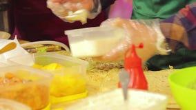 Alimento insalubre no cozinheiro do alimento-fest da rua que põe a maionese em uma refeição graxa video estoque