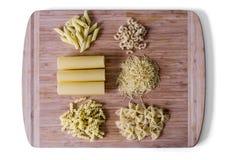 Alimento italiano - montão dos tubos do macarrão, dos espaguetes, dos macarronetes, da massa e do cannelloni - foco macio seletiv Imagem de Stock