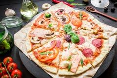 Alimento italiano Pizza com ingredientes, especiarias, óleo e vegetais no fundo escuro Configuração lisa, vista superior imagem de stock