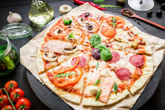Alimento italiano Pizza con los ingredientes, las especias, el aceite y las verduras en fondo oscuro Endecha plana, visión superi imagen de archivo