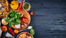 Alimento italiano Tomate de la albahaca de las pastas y aceite de oliva en copyspace rústico del wiith de la opinión superior del Fotos de archivo libres de regalías