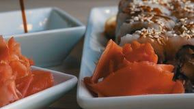 Alimento japonês Os rolos de sushi encontram-se na tabela ao lado do wasabi e do limão do gengibre O molho de soja é derramado de vídeos de arquivo