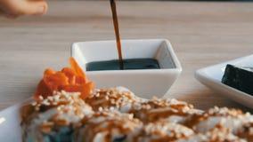 Alimento japonês Os rolos de sushi encontram-se na tabela ao lado do wasabi e do limão do gengibre O molho de soja é derramado de video estoque