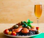 Alimento massa preta, camarões, tomates de cereja, vinho branco, de madeira Imagem de Stock Royalty Free