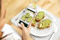 Alimento Mujer que toma las fotos de la comida en el teléfono imagen de archivo libre de regalías