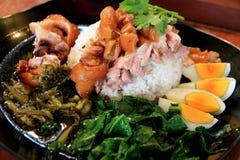 Alimento, pé da carne de porco do arroz, ovos cozidos, vegetais na placa preta Fotografia de Stock