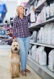 Alimento para animales de compra de la mujer para el perrito afgano del pastor en la tienda para el anim imagen de archivo