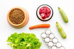 Alimento para animales seco con los ingredientes naturales Carne cruda, verduras calabacín y zanahoria cerca de los huevos en la  Fotos de archivo