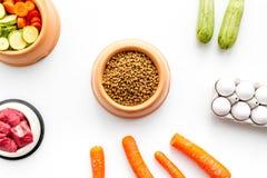 Alimento para animales seco con los ingredientes naturales Carne cruda, verduras calabacín y zanahoria cerca de los huevos en la  Fotografía de archivo