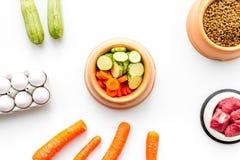 Alimento para animales seco con los ingredientes naturales Carne cruda, verduras calabacín y zanahoria cerca de los huevos en la  Foto de archivo libre de regalías
