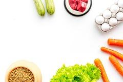Alimento para animales seco con los ingredientes naturales Carne cruda, verduras calabacín y zanahoria cerca de los huevos en la  Imagenes de archivo