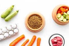 Alimento para animales seco con los ingredientes naturales Carne cruda, verduras calabacín y zanahoria cerca de los huevos en la  Fotografía de archivo libre de regalías