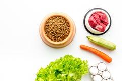 Alimento para animales seco con los ingredientes naturales Carne cruda, verduras calabacín y zanahoria cerca de los huevos en la  Fotos de archivo libres de regalías