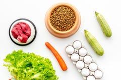 Alimento para animales seco con los ingredientes naturales Carne cruda, verduras calabacín y zanahoria cerca de los huevos en la  Imagen de archivo libre de regalías