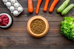 Alimento para animales seco con los ingredientes naturales La carne cruda, las verduras calabacín y la zanahoria cerca de los hue Foto de archivo libre de regalías