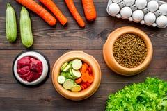 Alimento para animales seco con los ingredientes naturales La carne cruda, las verduras calabacín y la zanahoria cerca de los hue Imagenes de archivo
