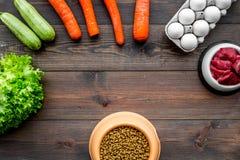 Alimento para animales seco con los ingredientes naturales La carne cruda, las verduras calabacín y la zanahoria cerca de los hue Fotos de archivo libres de regalías