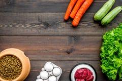 Alimento para animales seco con los ingredientes naturales La carne cruda, las verduras calabacín y la zanahoria cerca de los hue Fotografía de archivo libre de regalías