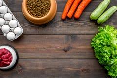 Alimento para animales seco con los ingredientes naturales La carne cruda, las verduras calabacín y la zanahoria cerca de los hue Fotos de archivo