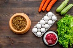 Alimento para animales seco con los ingredientes naturales La carne cruda, las verduras calabacín y la zanahoria cerca de los hue Imágenes de archivo libres de regalías