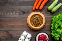 Alimento para animales seco con los ingredientes naturales La carne cruda, las verduras calabacín y la zanahoria cerca de los hue Imagen de archivo libre de regalías