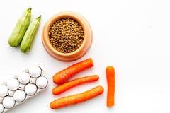 Alimento para animales seco con los ingredientes naturales Las verduras calabacín y zanahoria cerca de los huevos en la opinión s Foto de archivo