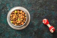 Alimento para cães na bacia metálica em escuro preto - fundo azul imagens de stock