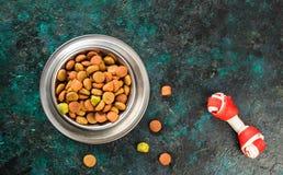 Alimento para cães na bacia metálica em escuro preto - fundo azul fotografia de stock