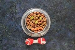 Alimento para cães na bacia metálica em escuro preto - fundo azul imagem de stock royalty free
