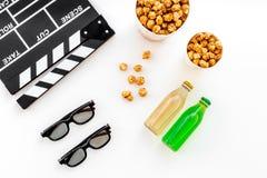 Alimento para o filme de observação Pipoca e soda perto do clapperboard, vidros no copyspace branco da opinião superior do fundo Fotos de Stock