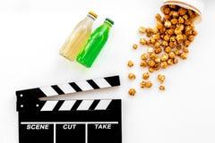 Alimento para o filme de observação Pipoca e soda perto do clapperboard, vidros no copyspace branco da opinião superior do fundo Imagens de Stock