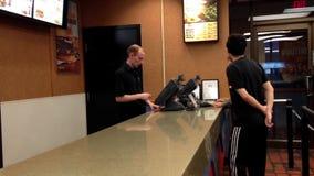 Alimento pedindo dos povos no contador de verificação geral de Burger King video estoque