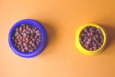 Alimento per animali domestici asciutto in ciotole variopinte immagine stock