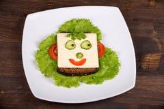 Alimento per i bambini - fronte di divertimento su pane Fotografie Stock