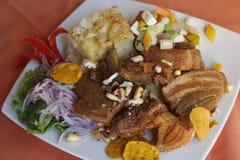 Alimento peruviano, Chicharron (carne di maiale fritta) con le patate, contorno della cipolla, canchita Immagini Stock