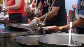 Alimento pronto pronto da mangiare di vendite della gente al mercato di strada sul partito del barbecue Movimento lento stock footage