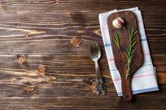 Alimento que cozinha o fundo com placa de corte, a cutelaria e as especiarias de madeira Vista superior imagem de stock