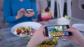 Alimento sano, la gente che per mezzo del telefono moderno per la foto di insalata vegetariana durante il brunch per le reti soci stock footage