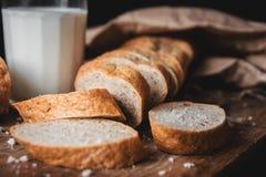 Alimento sano La pagnotta lunga di pane rurale con due pezzi di taglio si trova su un tagliere di legno e su un vetro di latte fr fotografia stock libera da diritti