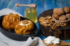 Alimento sano Mele al forno con la ricotta e bugia matta in un piatto bollente nero su una tavola di legno bianca fotografia stock libera da diritti