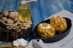 Alimento sano Mele al forno con la ricotta e bugia matta in un piatto bollente nero su una tavola di legno blu fotografie stock libere da diritti